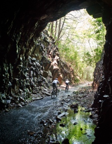 Mountain bikers riding through abandoned railroad tunnel in Coburn, PA by Abram Eric Landes